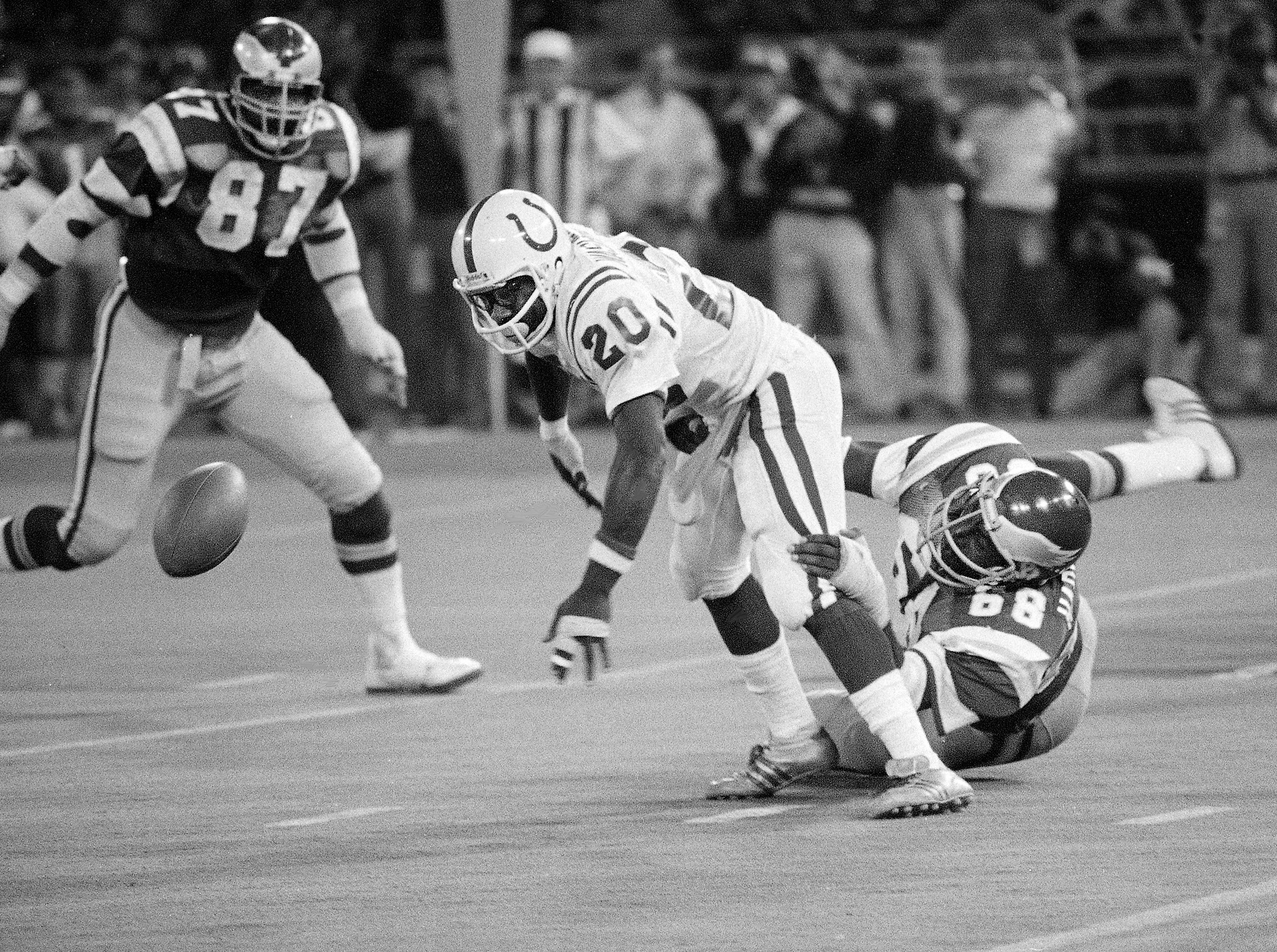 Baltimore Colts' halfback Joe Washington (20) fumbles the ball as he is grabbed from behind by Philadelphia Eagles' Dennis Harrison (68) in the first half of the preseason game in Philadelphia August 17, 1979. Watching is Eagles' Claude Humphrey (78) as the ball was recovered by the Colts.