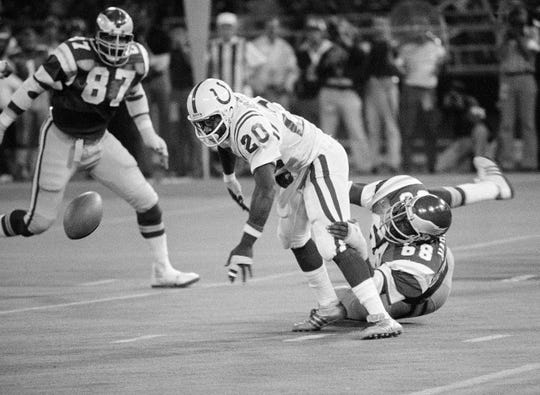 Baltimore Colts halfback Joe Washington (20) fumbles as he is grabbed from behind by the Eagles' Dennis Harrison (68) in the first half of a 1979 preseason game.