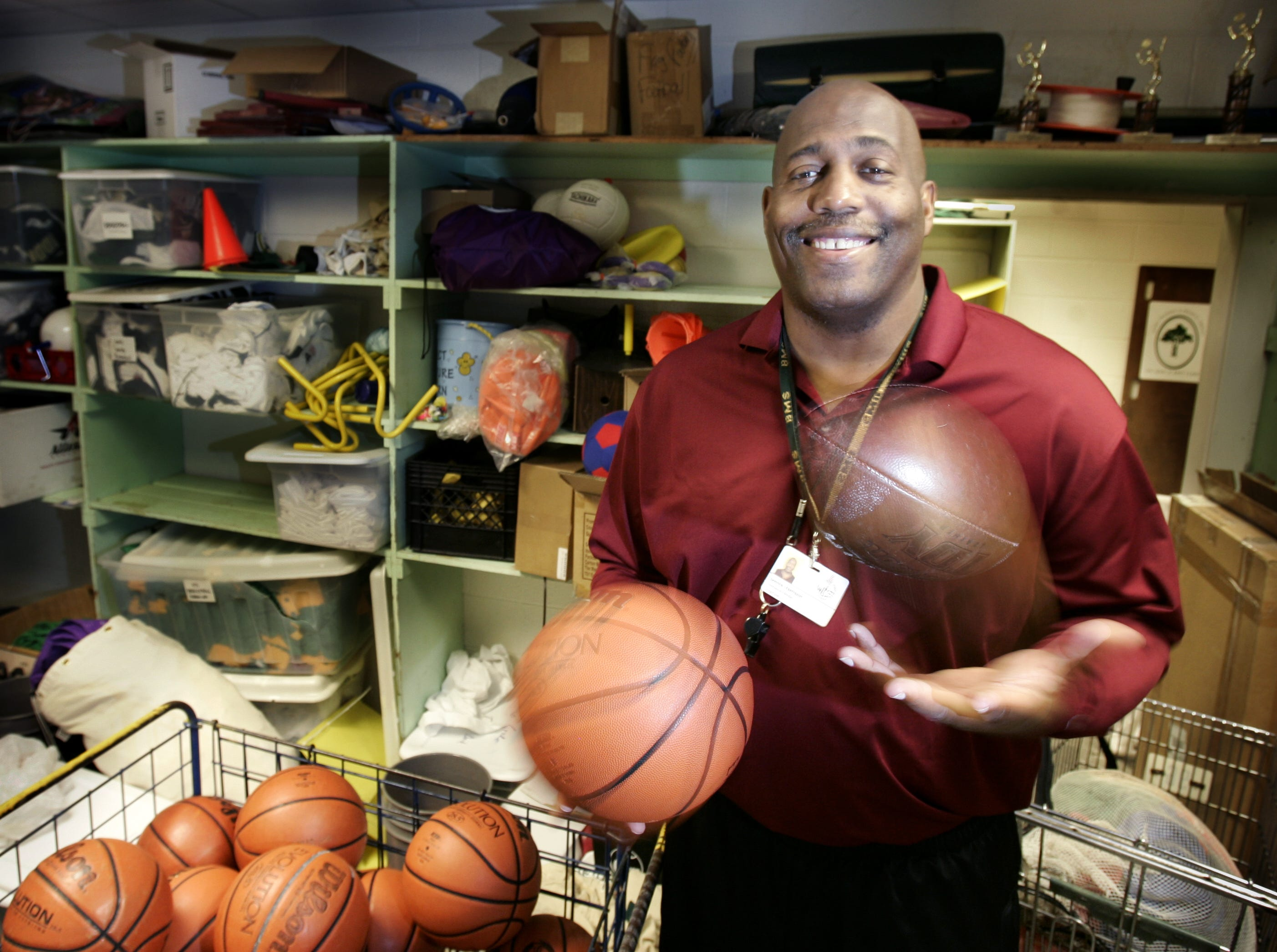 Former NFL player Dennis Harrison stands in the the supply closet at Brentwood Middle School where he teachers PE and coaches football, basketball, track, and wrestling.