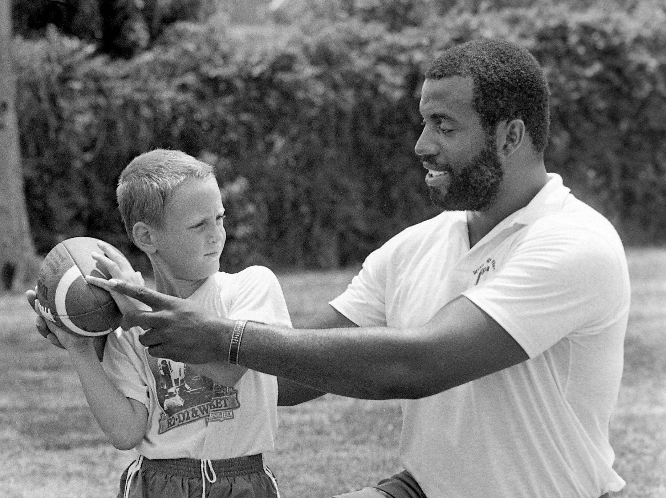 Philadelphia Eagles All Pro defensive end Dennis Harrison, right, offers some pointers to 7-year-old Bo Link during his annual football camp at Franklin Road Academy June 11, 1984. Harrison played at Murfreesboro Riverdale High and Vanderbilt University.