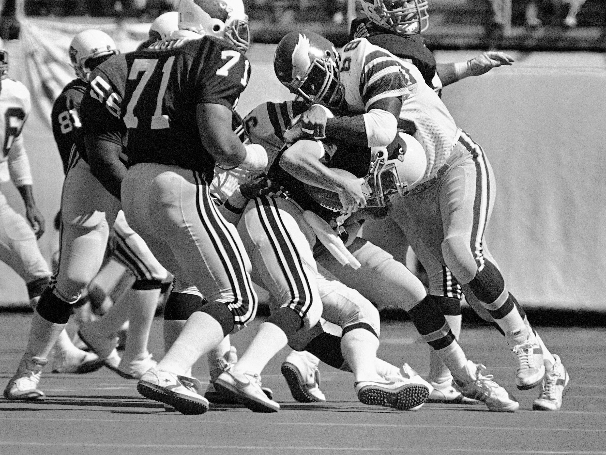 St. Louis Cardinals quarterback Jim Hart, center, is sacked for a five yard loss by Philadelphia Eagles defensive end Dennis Harrison late in the first quarter of play at Veterans Stadium in Philadelphia on Sept. 25, 1983. (AP Photo/Rusty Kennedy)