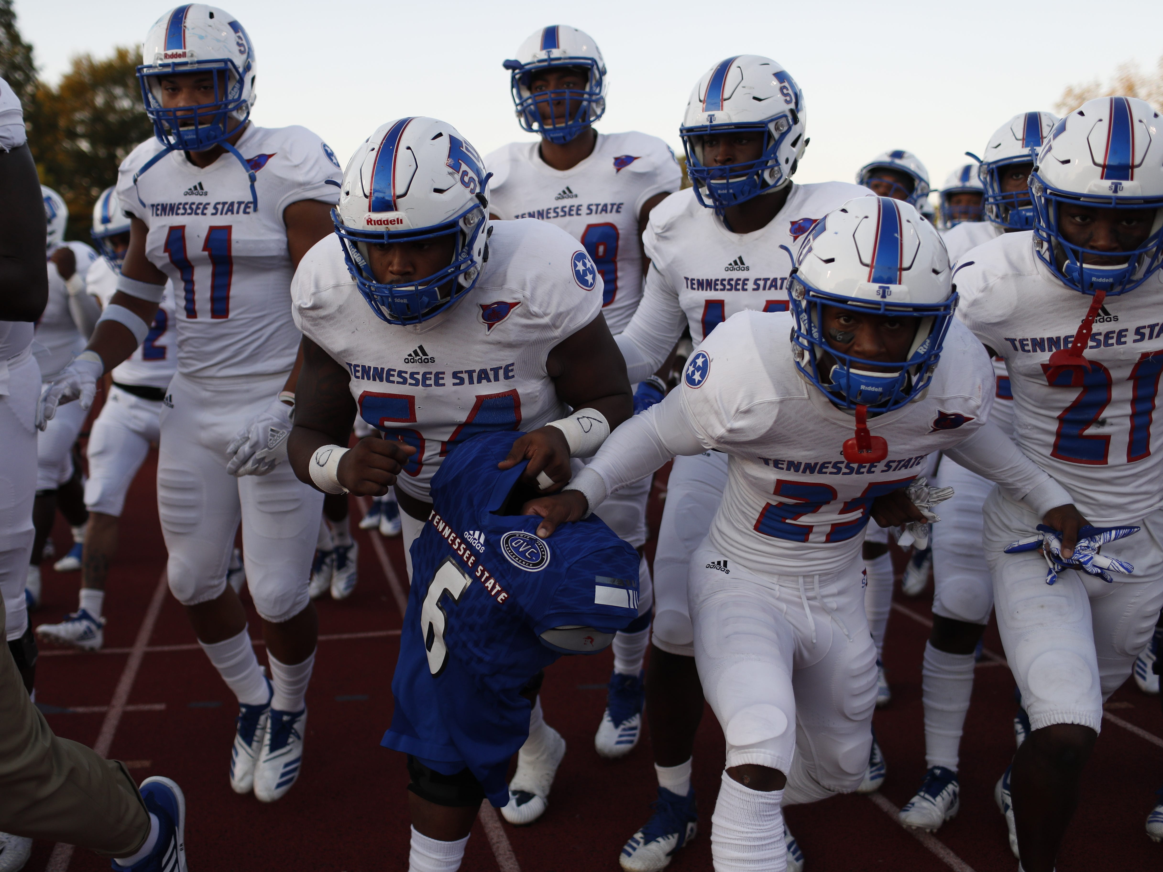 Tennessee State players hold the shoulder pads and jersey of Christion Abercrombie as they walk out onto the field before the Tigers' game at Austin Peay on Saturday, October 6, 2018.