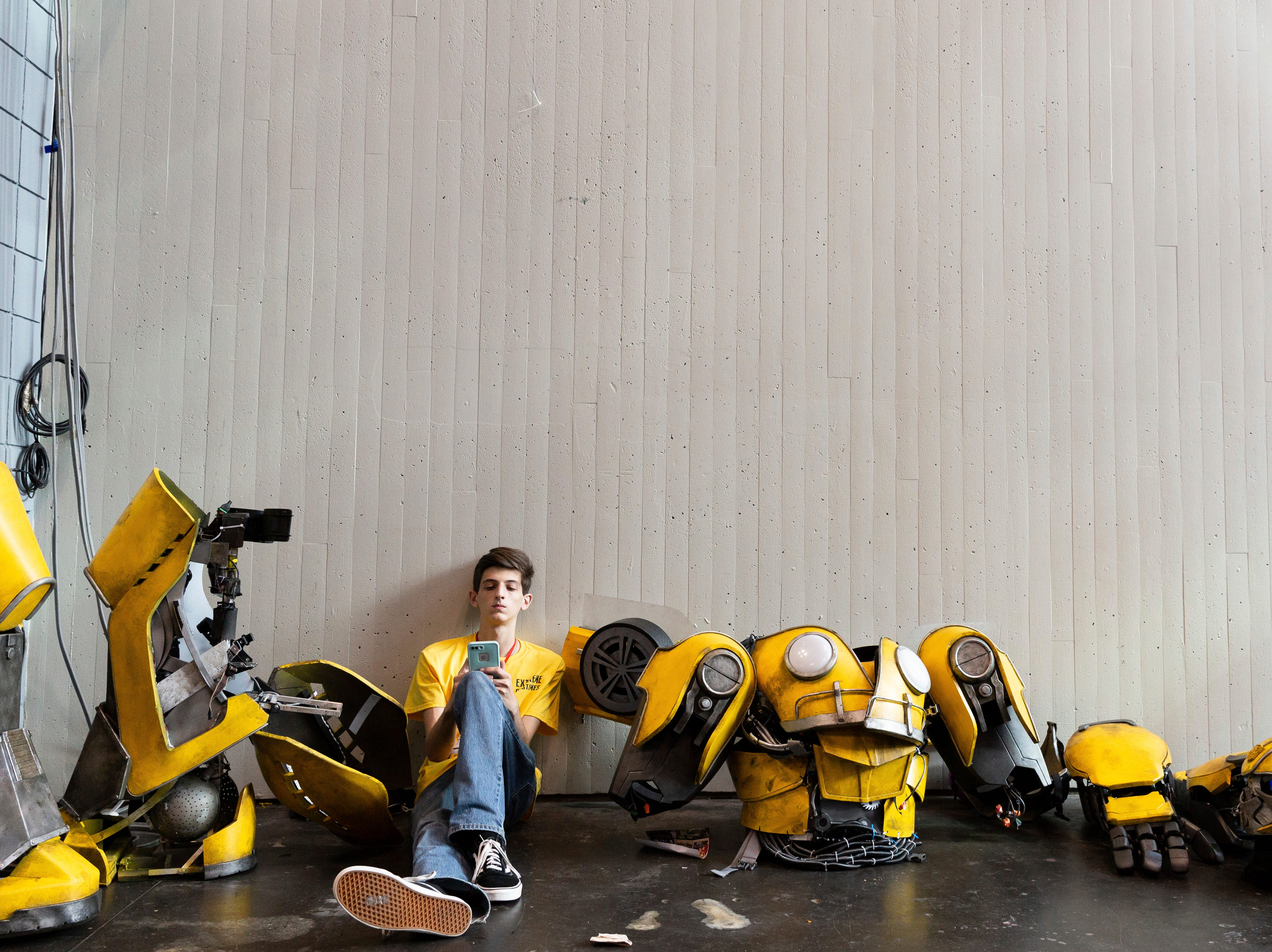A man sits against a wall next to pieces of a costume on the second day of New York Comic Con, Friday, Oct. 5, 2018. (AP Photo/Steve Luciano)