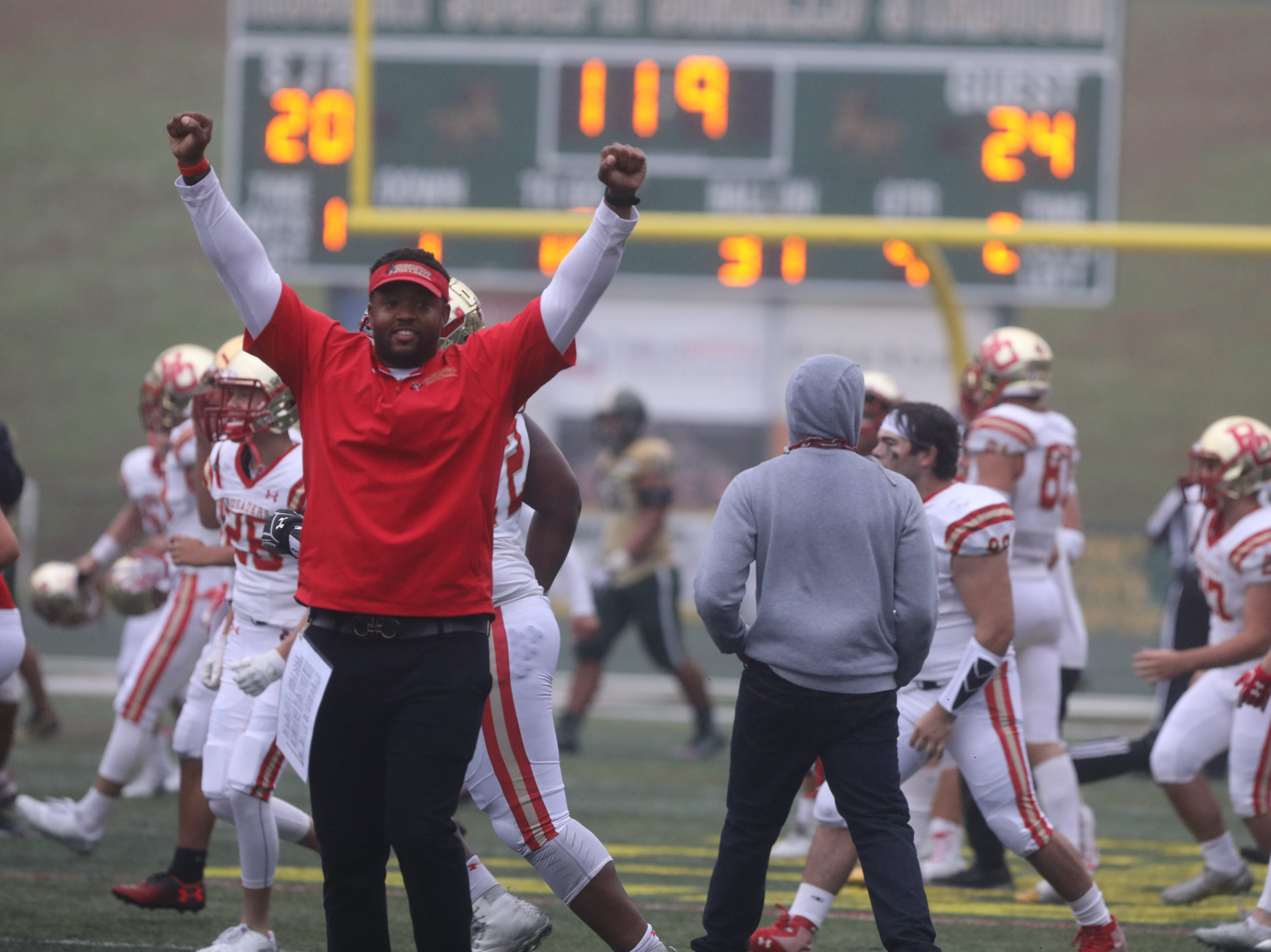 Assistant coach Darnell Carter celebrates his team's win at the end off the game.