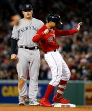 Boston Red Sox's Mookie Betts, right, celebrates after a double against the New York Yankees during the third inning of Game 1 of a baseball American League Division Series on Friday, Oct. 5, 2018, in Boston.