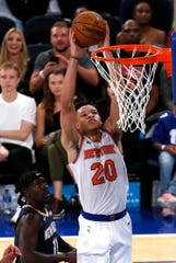 Oct 5, 2018; New York, NY, USA;  New York Knicks forward Kevin Knox (20) dunks against New Orleans Pelicans guard Jrue Holiday (11) during the second quarter at Madison Square Garden.