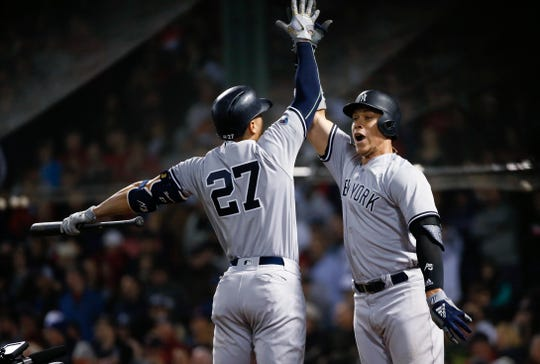 New York Yankees' Aaron Judge celebrates his home run with Giancarlo Stanton (27) during the ninth inning of Game 1 of a baseball American League Division Series against the Boston Red Sox on Friday, Oct. 5, 2018, in Boston.
