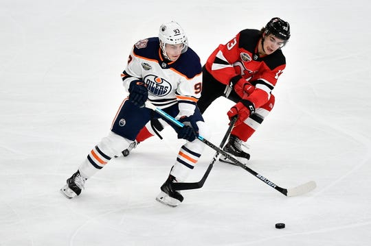 Edmonton Oilers' Ryan Nugent-Hopkins and New Jersey Devils' Nico Hischier vie for the puck, during the season-opening NHL Global Series hockey match between Edmonton Oilers and New Jersey Devils at Scandinavium in Gothenburg, Sweden, Saturday, Oct. 6, 2018