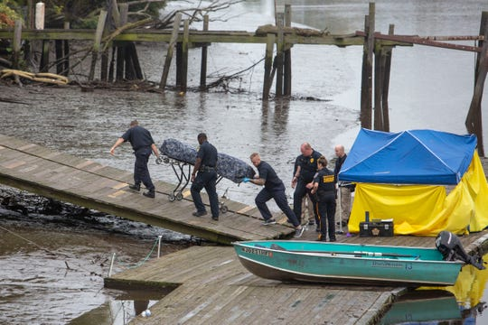 Workers remove a body from the docks of the Kearny Boathouse where North Arlington rescue workers docked after recovering a body from the Passaic River on Saturday, October 6 2018.
