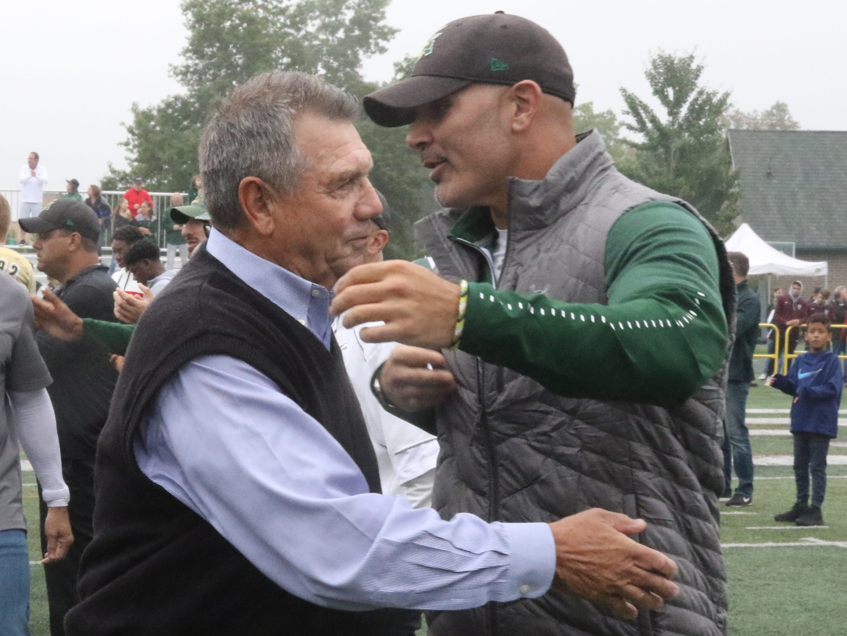 Former St. Joseph Coach, Tony Karcich hugs present St. Joseph coach Augie Hoffman as part of a ceremony honoring Karcich and naming the St. Joseph field after him.