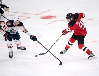 Edmonton Oilers' Matt Benning, left and New Jersey Devils' Taylor Hall vie for the puck, during the season-opening NHL Global Series hockey match between Edmonton Oilers and New Jersey Devils at Scandinavium in Gothenburg, Sweden, Saturday, Oct. 6, 2018