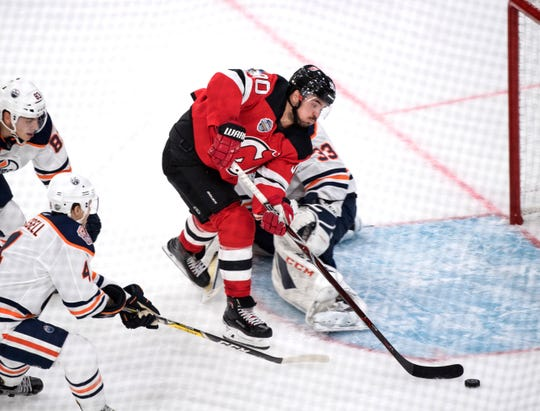 New Jersey Devils' Marcus Johansson passes Edmonton Oilers' goalie Cam Talbots, during the season-opening NHL Global Series hockey match between Edmonton Oilers and New Jersey Devils at Scandinavium in Gothenburg, Sweden, Saturday, Oct. 6, 2018