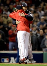 Boston Red Sox manager Alex Cora and New York Yankees manager Aaron Boone hug before Game 1 of a baseball American League Division Series on Friday, Oct. 5, 2018, in Boston.