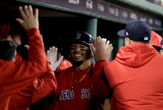 Boston Red Sox's Mookie Betts celebrates in the dugout after scoring of a single by Steve Pearce during the third inning of Game 1 of a baseball American League Division Series against the New York Yankees on Friday, Oct. 5, 2018, in Boston.