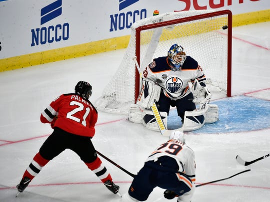 New Jersey Devils' Kyle Palmieri, left, scores, during the season-opening NHL Global Series hockey match between Edmonton Oilers and New Jersey Devils at Scandinavium in Gothenburg, Sweden, Saturday, Oct. 6, 2018