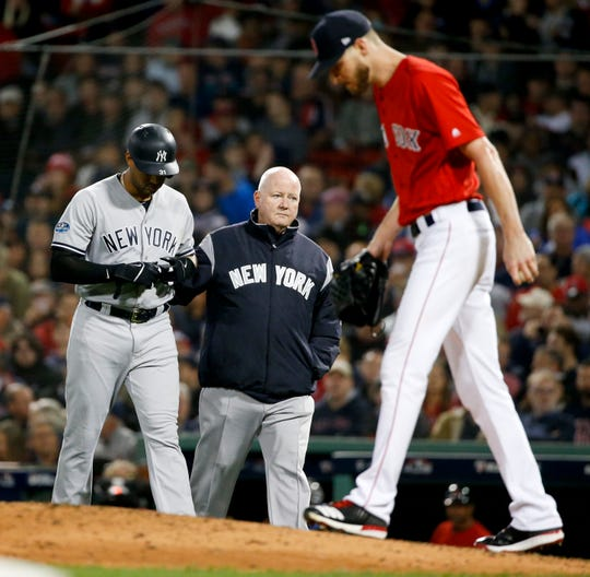 New York Yankees' Aaron Hicks, left, is helped off he field after getting hurt during the fourth inning of Game 1 of the baseball team's American League Division Series against the Boston Red Sox on Friday, Oct. 5, 2018, in Boston.