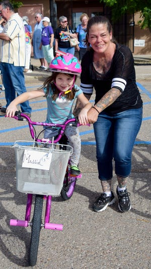 Lake Kids Club participant Maddie Montano receives assistance from her mother, Darsy, as she learns to ride her new bicycle.