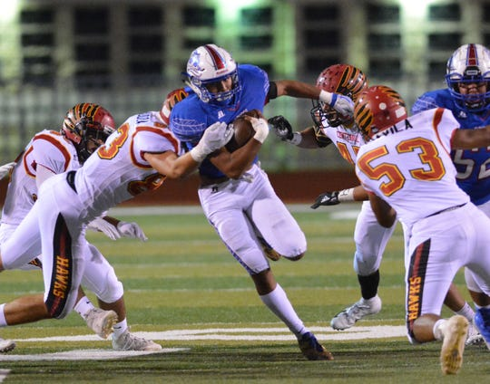 Las Cruces High's Ivan Molina breaks the tackle attempt by Jordan Mendoza as Centennial linebacker Damian Davila (53) gets ready to make a play Friday night at the Field of Dreams.