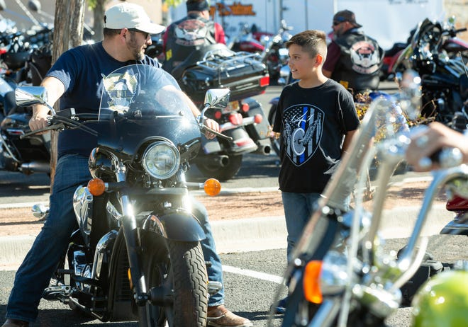 Santino Hernandez, left, and his son Jacob Hernandez wear T-shirts honorinng their late godfather JR Stewart during the Back the Blue Motorcycle Run on Saturday, Oct. 6, 2018 at Barnett's Las Cruces Harley-Davidson. Stewart, a retired Las Cruces Police officer, was killed last November in a motorcycle crash. Funds raised from the event will benefit the JR Stewart 141 Foundation.