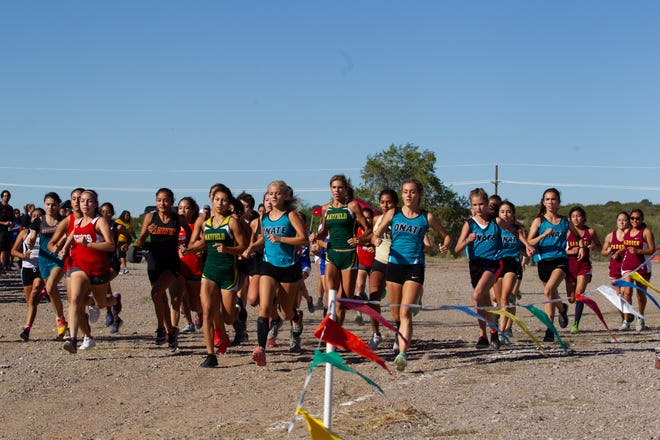 Girls varsity cross country participants round the first turn at the start of their race at the Centennial Invitational Saturday morning at Centennial High School.
