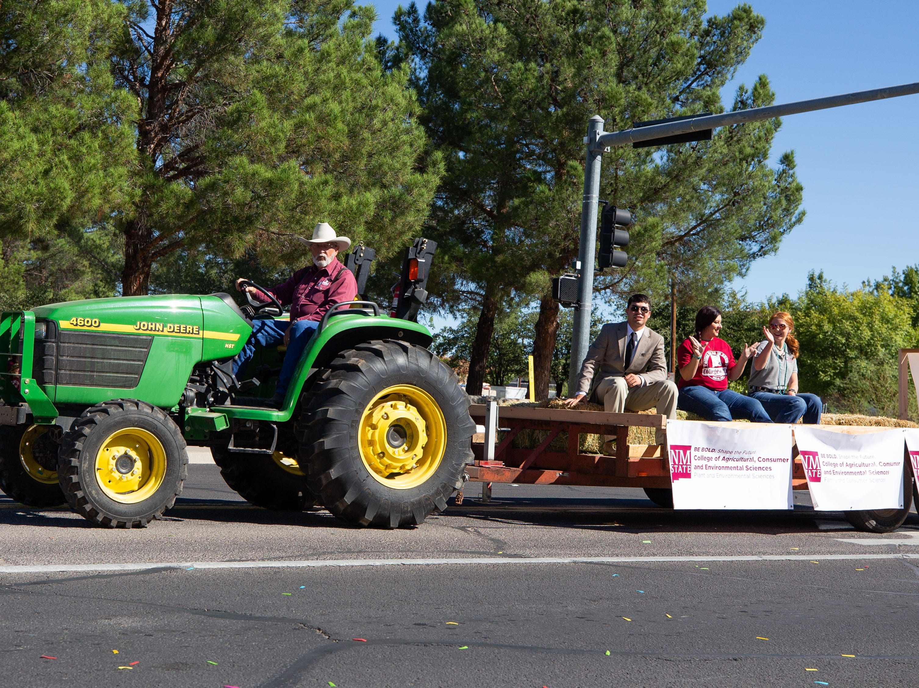 College of Agriculture, Consumer and Environmental Sciences float pulled by former Dean Jerry Schickedanz on a John Deere tractor at the NMSU Homecoming Parade on October 6, 2018.