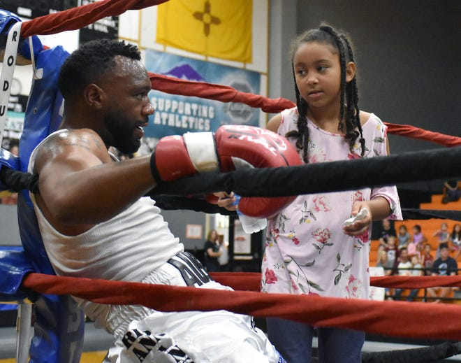 "Charlotte Trout, 8-year-old daughter of former boxing champion Austin ""No Doubt"" Trout, gives her father some water and advise between rounds during an charity event to raise money for the local CARE organization, Saturday Oct. 6, 2018  at Onate High School."