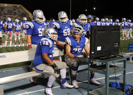 Crimson McKenzie (59) and the rest of the offensive linemen look over game film during Carlsbad's game against Gadsden in 2019.