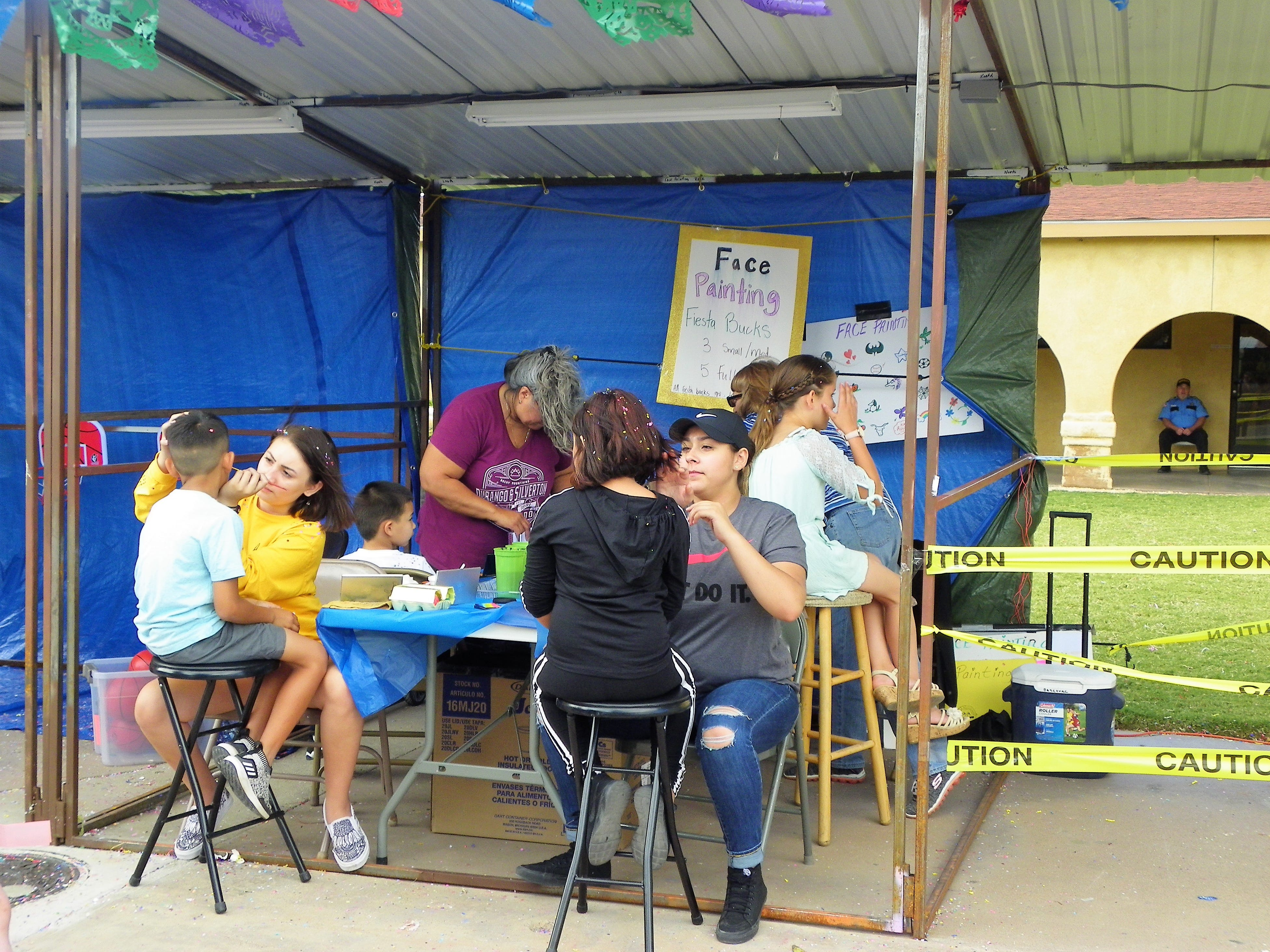 Volunteers paint children's faces at Immaculate Conception's Fiesta de la Familia Saturday