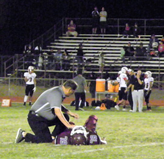 Wildcats Coach Richard Grace checks out Junior Shane Evans after he took a spill at the Tularosa High School Game versus the Hatch Valley Bears.