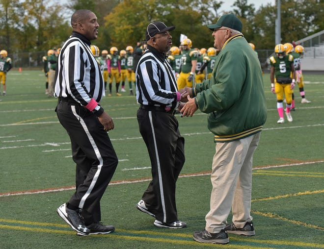Former Harrison coach John Herrington greets refs Lake Cosby and Lavon Brown during a 2018 game.