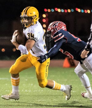 Fordson running back Abraham Jaafar (34) tries to break the grasp of Franklin tackler Arsell Weary.