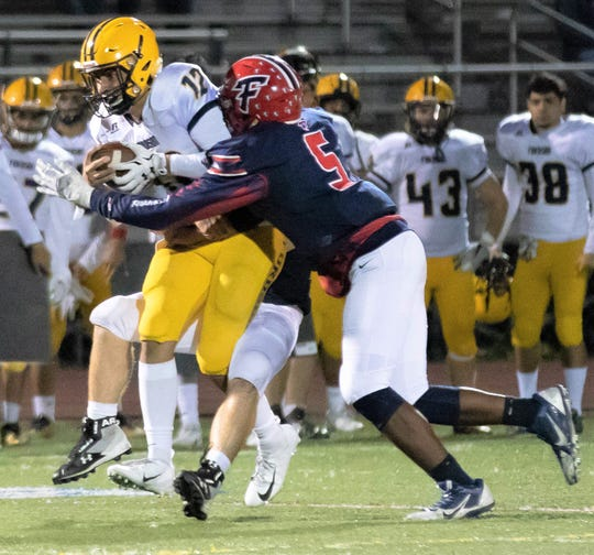 Franklin's Arsell Weary (right) sacks Fordson quarterback Hussein Ajami.