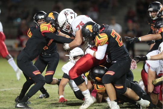 Palm Springs' Mike Glasson pushes for a first down against  Palm Desert on Friday, October 5, 2018 in Palm Desert.