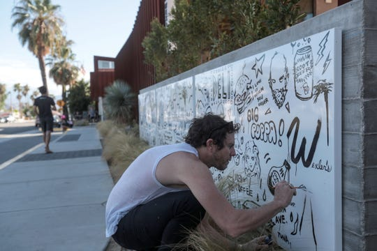 Artist Gregory Siff adds a road and sunset drawing to his mural for Wexler's deli at the Arrive Hotel in Palm Springs, on Saturday, October 6, 2018.