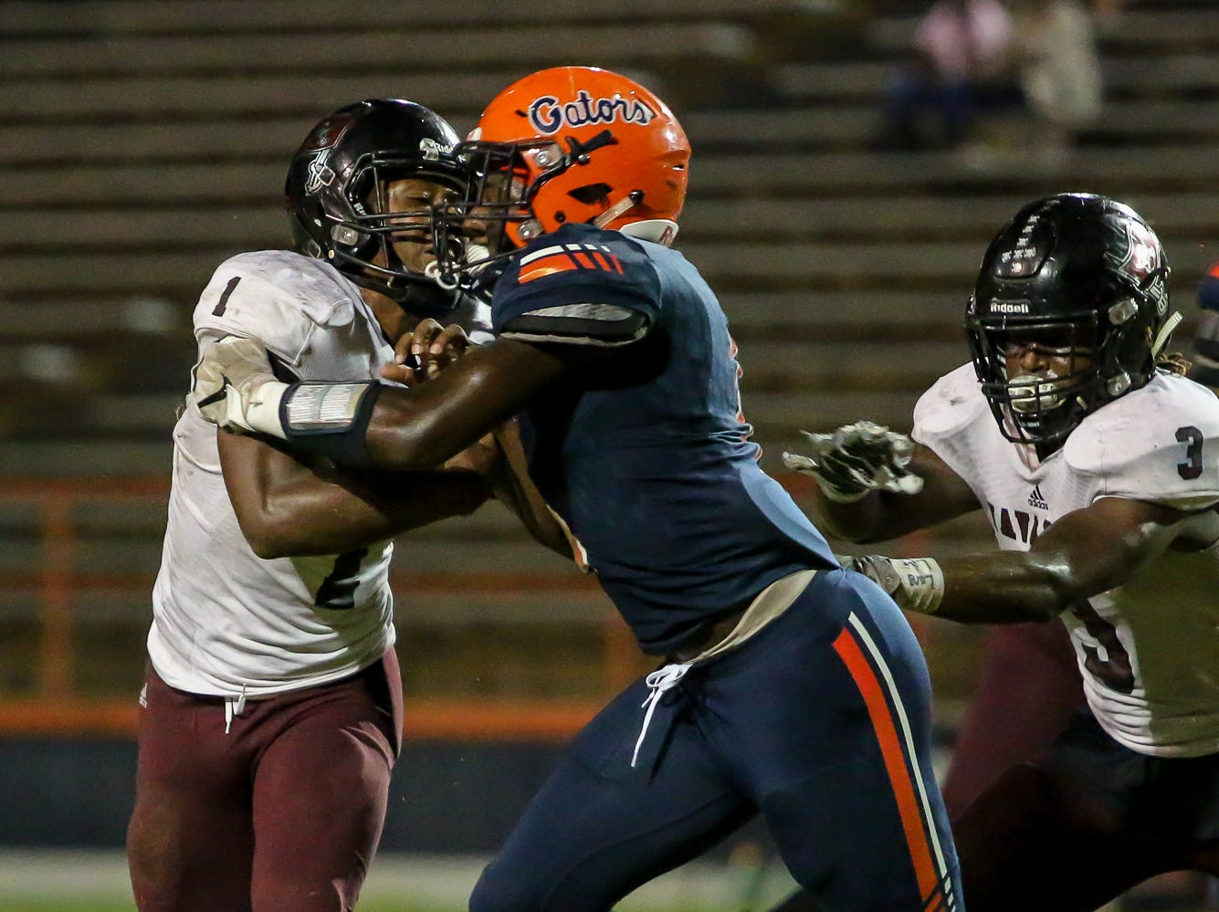 Escambia's Frank Peasant (1) pushes Navarre quarterback Marlon Courtney III (1) backward for a loss in the homecoming game at Escambia High School on Friday, October 5, 2018.