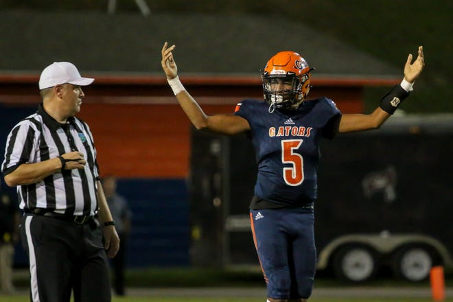 Escambia quarterback AV Smith (5) motions for the play call against Navarre in the homecoming game at Escambia High School on Friday, October 5, 2018.