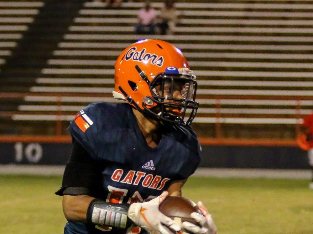 Escambia's Jaylen Blackmon (14) returns a Navarre kickoff in the homecoming game at Escambia High School on Friday, October 5, 2018.