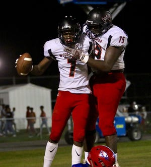 West Florida High's Keion Burrell, left, and Darius Washington celebrate after Burrell scored a touchdown against Pine Forest on Friday night at Pine Forest. (Oct. 5, 2018)