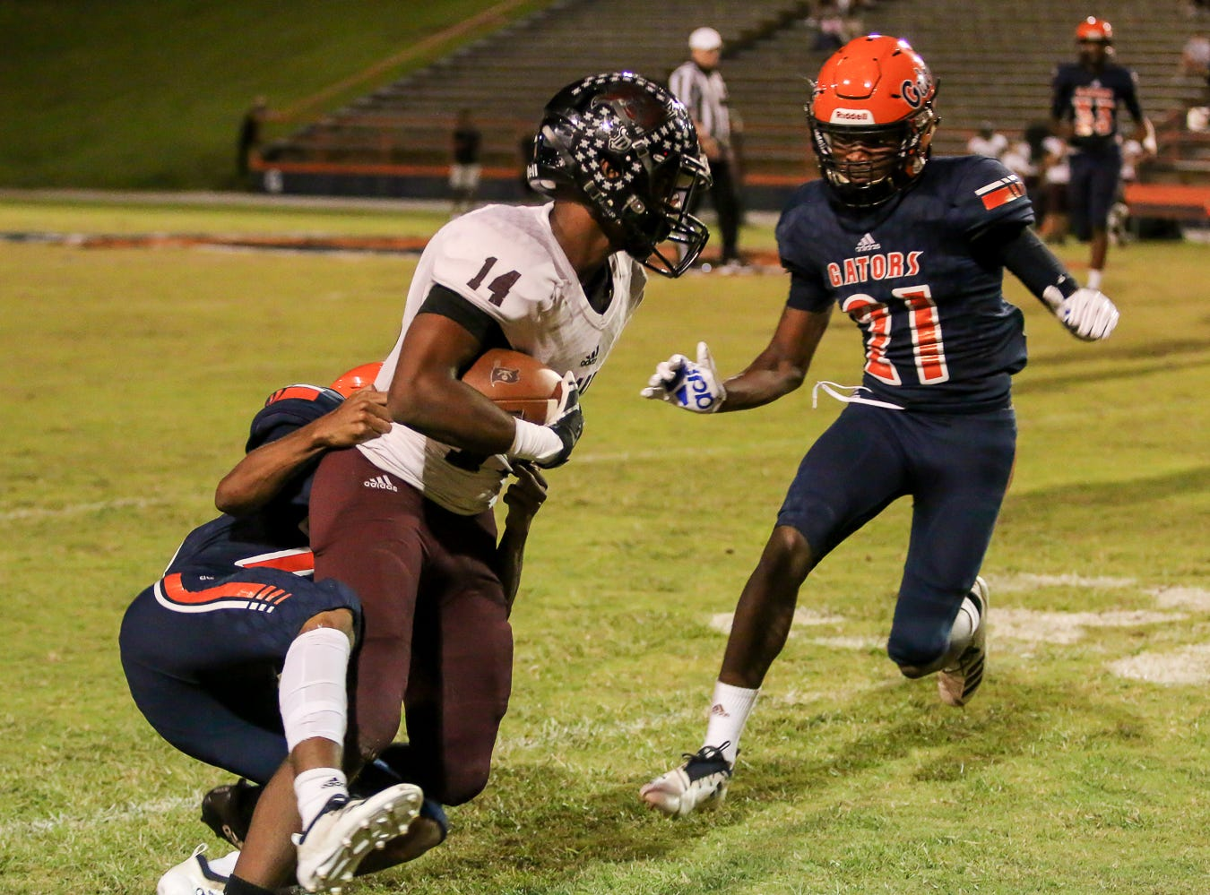 Navarre wide receiver Quinn Caballero (14) gets taken down by a Gators defender in the homecoming game at Escambia High School on Friday, October 5, 2018.