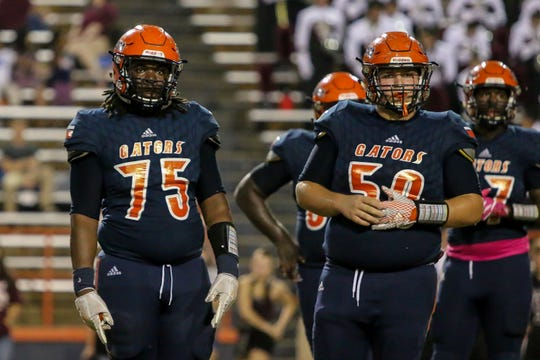 Gators Aric Harris (75) and Brennan Smith (50) look to the sideline for the play call against Navarre  in the homecoming game at Escambia High School on Friday, October 5, 2018.