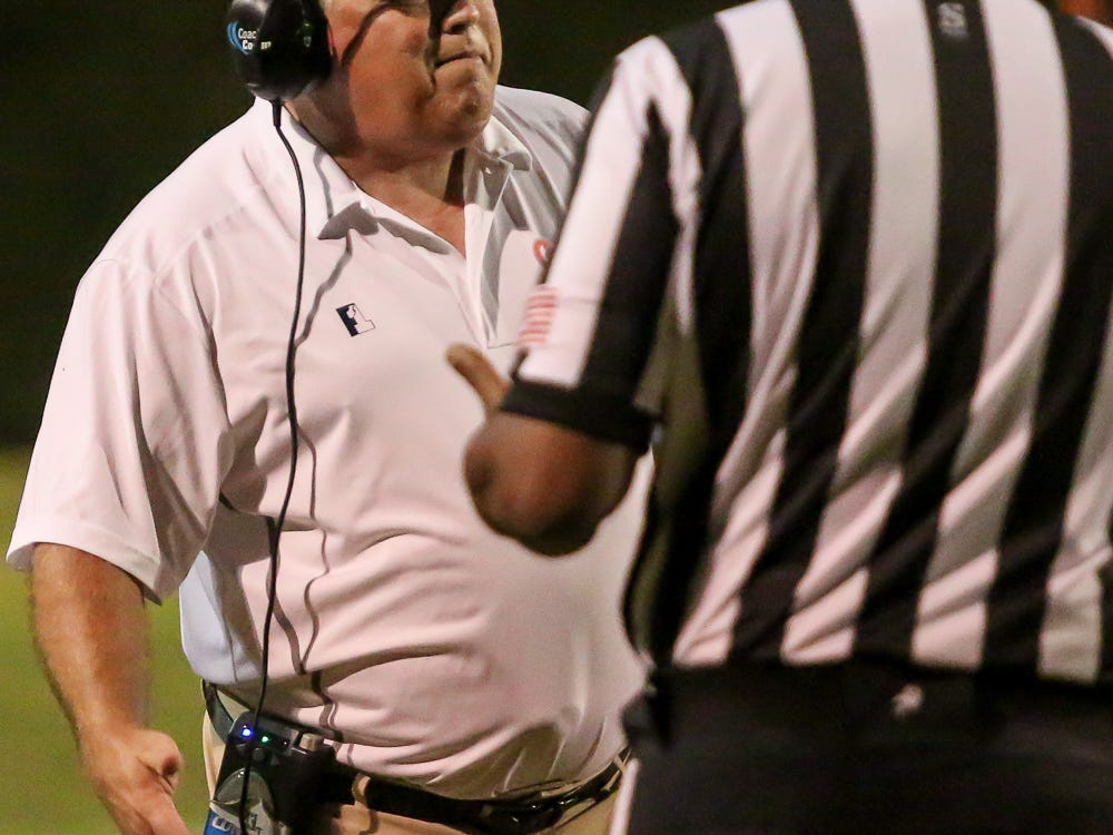 Escambia head coach Mike Bennett has a chat with an official during the homecoming game against Navarre at Escambia High School on Friday, October 5, 2018.