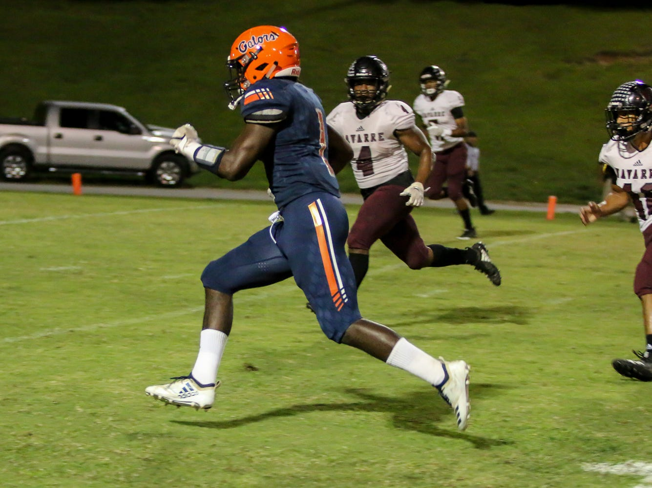 Escambia running back Frank Peasant (1) sprints past the Navarre defenders for and heads to the end zone in the homecoming game at Escambia High School on Friday, October 5, 2018.