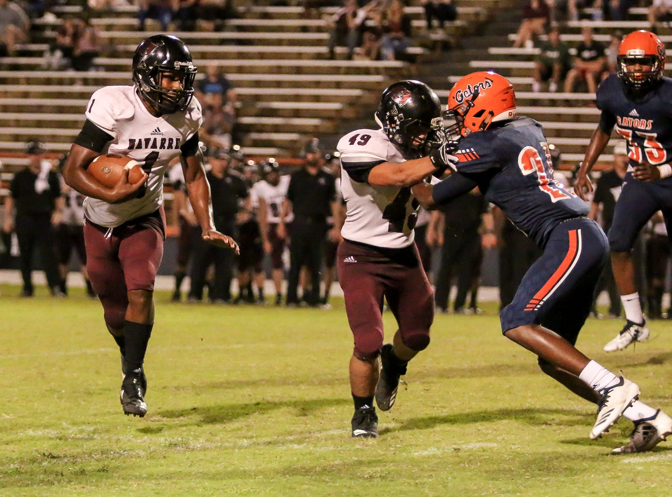 After faking a hand off to Dante Wright, not pictured, Navarre quarterback Marlon Courtney III (1) keeps the ball and follows his lead blocker, Fernando Gomez (49), for positive yards against the Gators in the homecoming game at Escambia High School on Friday, October 5, 2018.