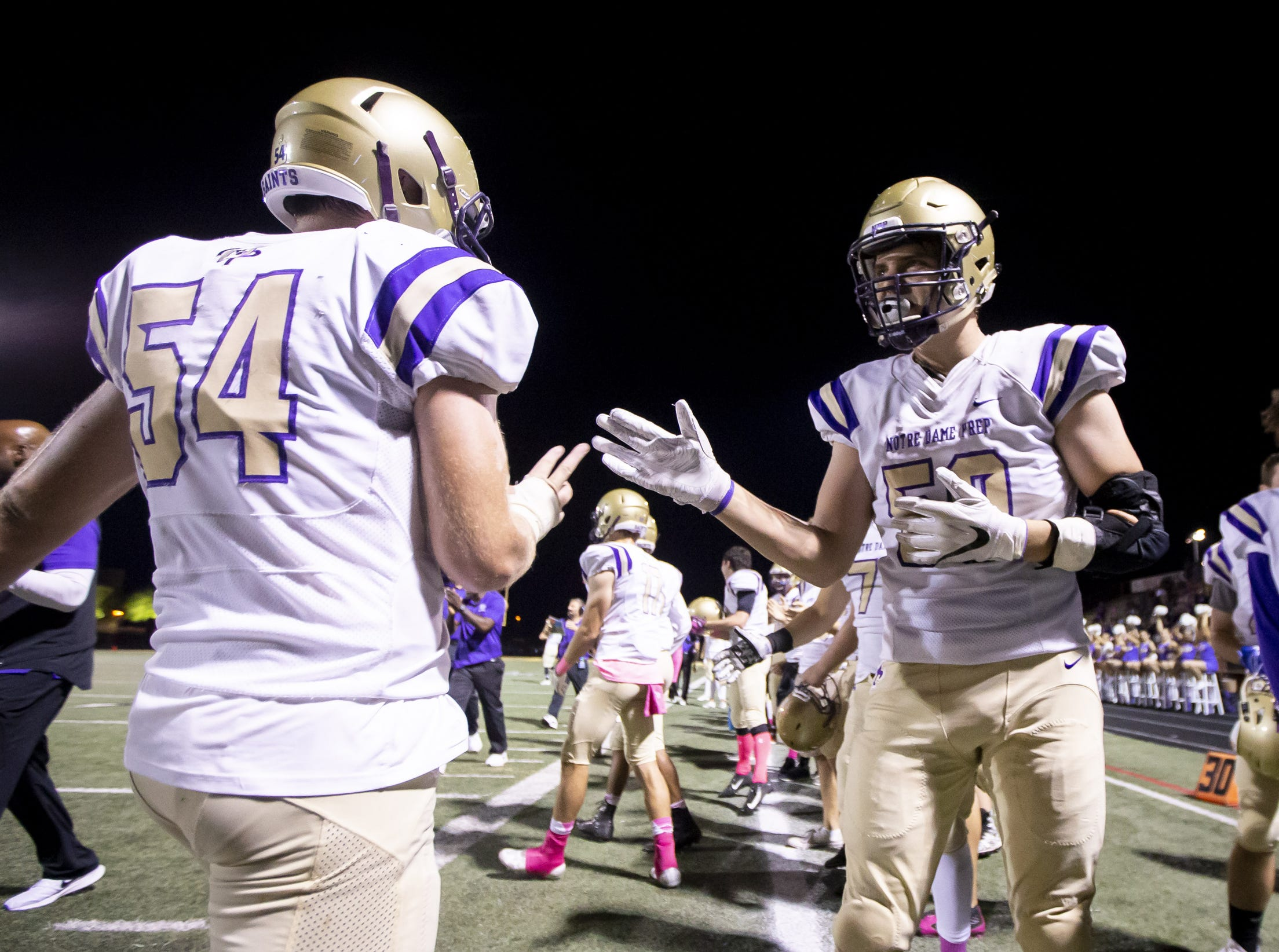 Notre Dame Prep Saints high-five following a score against the Horizon Huskies at Horizon High School on Friday, October 5, 2018 in Scottsdale, Arizona. #azhsfb