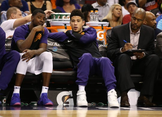 Phoenix Suns Josh Jackson and Devin Booker talk on the bench against the Portland Trail Blazers during a preseason game at Talking Stick Resort Arena on Oct. 5, 2018, in Phoenix, Ariz.
