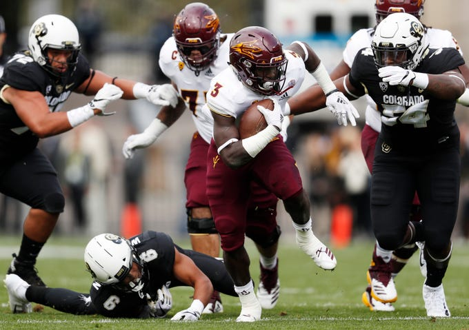 Arizona State running back Eno Benjamin, center, runs between Colorado defensive back Evan Worthington, left, and defensive lineman Mustafa Johnson for a long gain in the first half of an NCAA college football game Saturday, Oct. 6, 2018, in Boulder, Colo. (AP Photo/David Zalubowski)