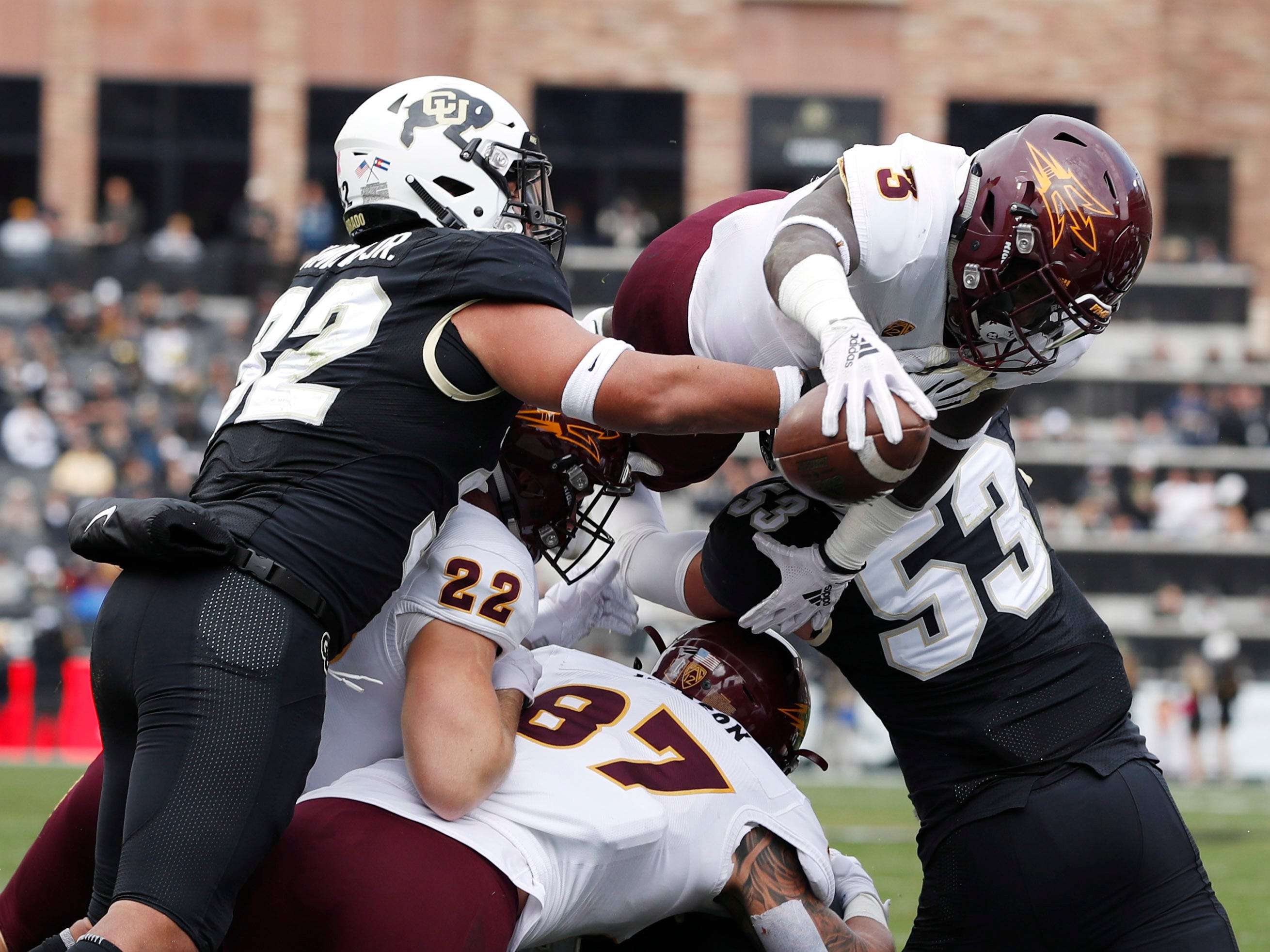 Arizona State running back Eno Benjamin, center, flies over Colorado linebackers Rick Gamboa, left, Nate Landman for a touchdown in the first half of an NCAA college football game Saturday, Oct. 6, 2018, in Boulder, Colo. (AP Photo/David Zalubowski)