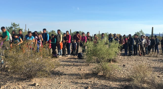 Humanitarian Crisis: A group of 163 migrants, most from Guatemala, stand in a line as the Border Patrol determines where to send them.