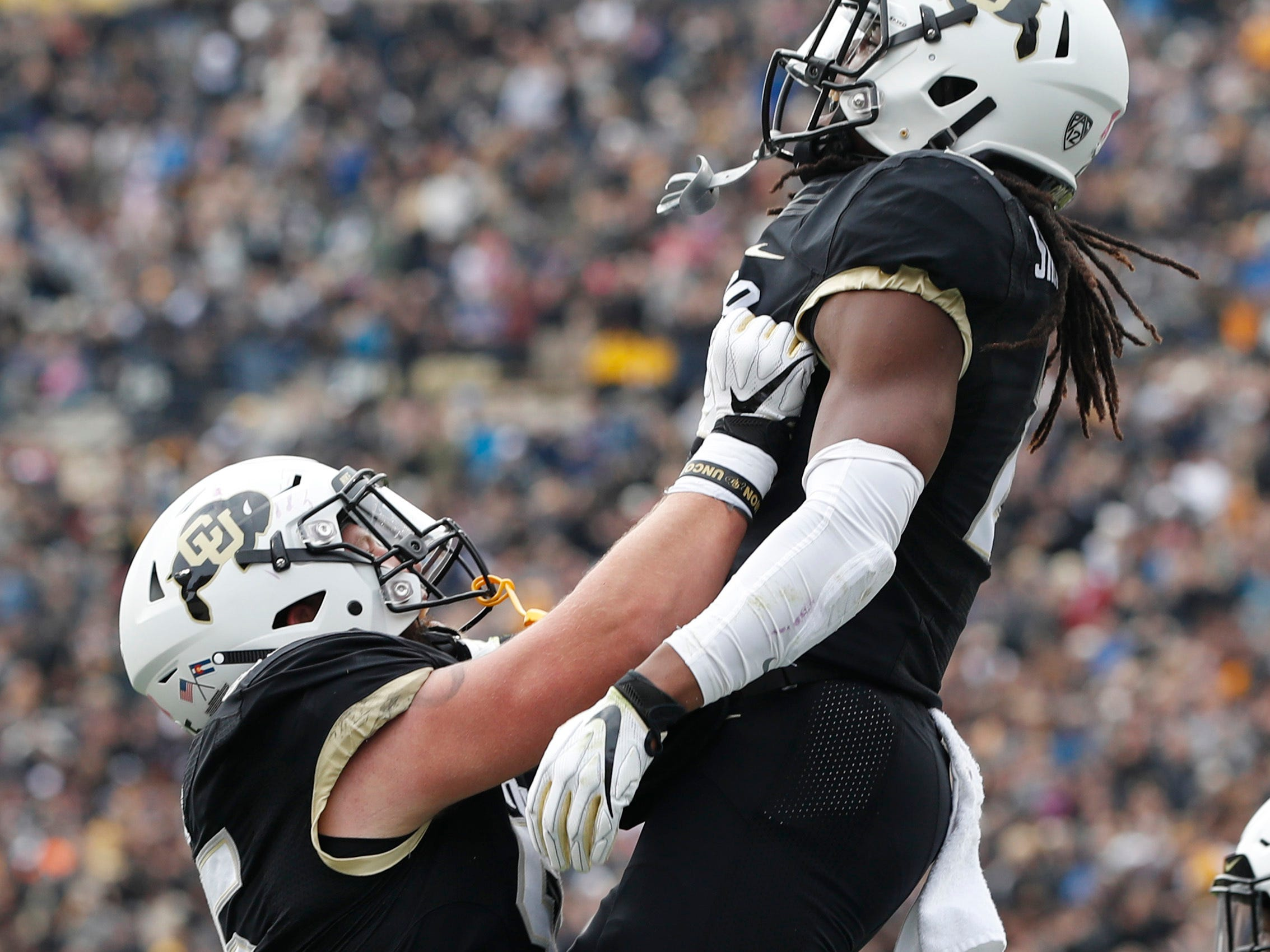 Colorado offensive lineman Brett Tonz, left, hoists wide receiver Laviska Shenault Jr. into the air to celebrate his run for a touchdown against Arizona State in the first half of an NCAA college football game Saturday, Oct. 6, 2018, in Boulder, Colo. (AP Photo/David Zalubowski)