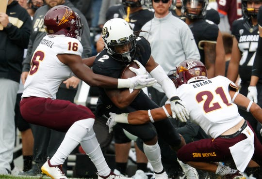 Colorado wide receiver Laviska Shenault Jr., center, is tackled after catching a pass by Arizona State safety Aashari Crosswell, left, and cornerback Terin Adams after the second half of an NCAA college football game Saturday, Oct. 6, 2018, in Boulder, Colo. Colorado won 28-21. (AP Photo/David Zalubowski)